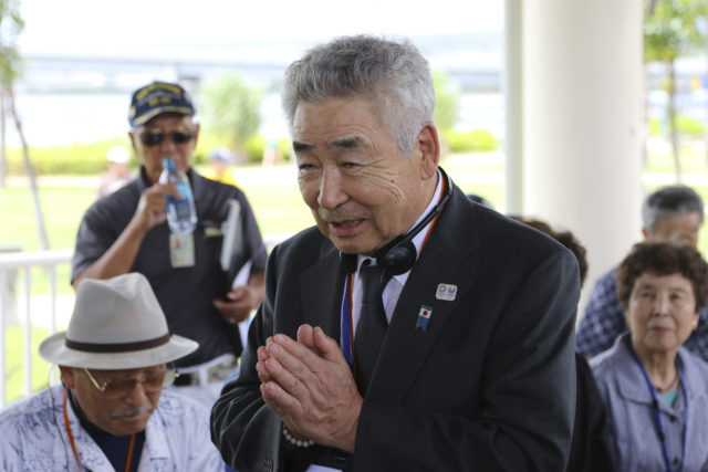 Yukio Udagawa, vice president of Nippon Izokukai, the Bereaved Family Association of Japan, speaks to Japanese-Americans before a ceremony at the USS Arizona Memorial in Pearl Harbor, Hawaii, Thursday, Sept. 21, 2017. Dozens of descendants of Japanese soldiers killed in World War II visited Pearl Harbor on Thursday to pay respects to American war dead. Nippon Izokukai sent about 36 children, grandchildren and other relatives of fallen Japanese soldiers to the U.S. to mark the 70th anniversary of the group's founding. With the rusted hull of the USS Arizona beneath them, the group laid flowers and a wreath at the memorial after touring the Pacific Aviation Museum and the USS Missouri at Pearl Harbor. (AP Photo/Caleb Jones)