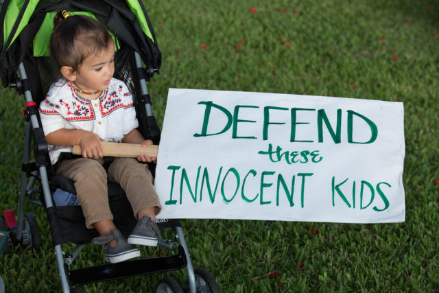 A child holds a sign at the Honolulu rally to protest the decision to rescind