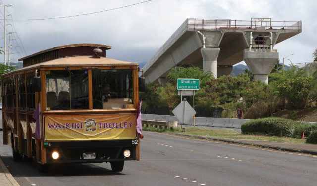 HART Rail guideway along Kamehameha Hwy near the Aloha Stadium with Waikiki Trolley at left.