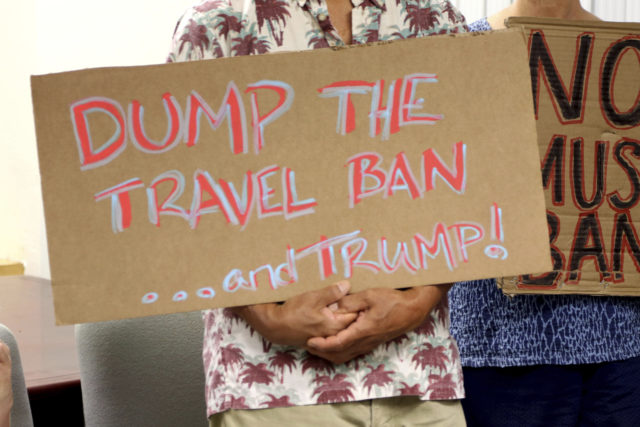 FILE- In this June 30, 2017, file photo, critics of President Donald Trump's travel ban hold signs during a news conference in Honolulu. The Trump administration is appealing a Hawaii judge's order that blocks the newest version of the travel ban. Attorneys for the U.S. government filed court papers Tuesday, Oct. 24, 2017, saying they are taking the case to the 9th U.S. Circuit Court of Appeals. The appeals court has blocked both of Trump's previous bans. (AP Photo/Caleb Jones, File)