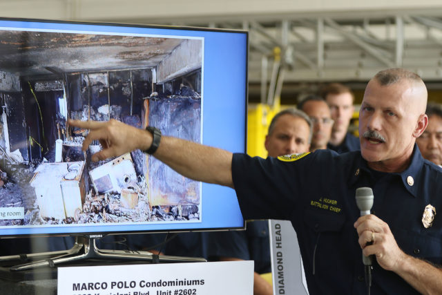 Battalion Chief J. Hooker points to areas in burned out unit 2602 at Marco Polo during press conference held at the McCully fire station.
