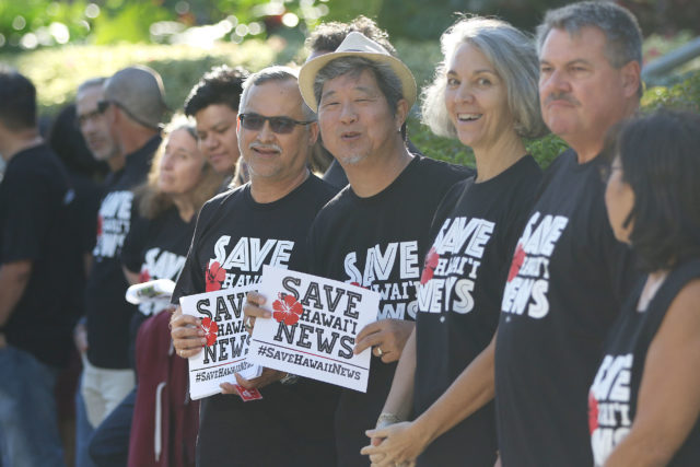 Star Advertiser staffers Rob Perez, left and right, Bryant Fukutomi hold signs Save Hawaii News outside the Honolulu Star Advertiser offices.