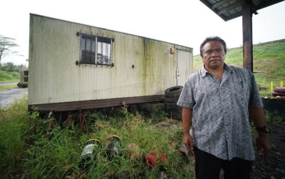 Michael Makekau stands fronting the old portable building he was sickened by mold from an airconditioner at the Hilo landfill. Portable building can be seen at right of photograph.