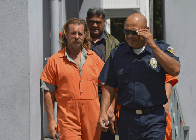 FILE - In this Oct. 4, 2016, file photo provided by the Samoa News, Dean Jay Fletcher, left, is escorted by a police officer after his initial appearance in the District Court of American Samoa in Pago Pago, American Samoa. A U.S. judge in Hawaii has ordered the release of U.S. citizen Fletcher, being held for extradition to Tonga, where he's accused of beating his wife to death, escaping police and sailing some 300 miles to American Samoa. (Ausage Fausia/SamoaNews via AP, File)