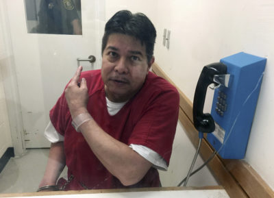 Escaped hospital patient Randall Saito points to a guard as he sits in an inmate visitor's booth at San Joaquin County Jail before a scheduled court hearing in French Camp, Calif., Friday, Nov. 17, 2017. Saito, who escaped from a psychiatric hospital in Hawaii, was captured as the result of a tip from a taxi cab driver. (AP Photo/Terry Chea)