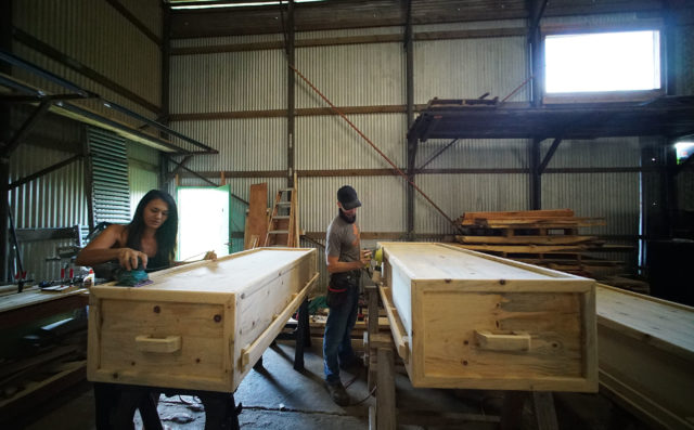 Left Cortney Gusick, founder and 'Casketeer' at Pahiki Eco-Caskets works with casket builder Logan Baggett at their warehouse workshop in Waimanalo.
