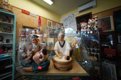 Surf n Hula ceramic collectibles and a 'maneki neko' on display in the shop.