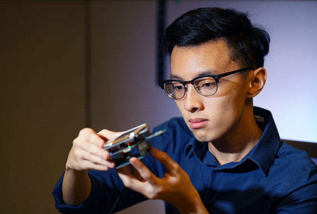 Christopher Nguyen holds a device that will eventually be mounted in a drone to make photographs of storm damaged areas.