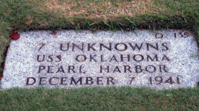 FILE - In this Dec. 5, 2012 file photo, a gravestone identifying the resting place of 7 unknowns from the USS Oklahoma is shown at the National Memorial Cemetery of the Pacific in Honolulu. The military says it has identified 100 sailors and Marines killed when the USS Oklahoma capsized during the Japanese bombing of Pearl Harbor 76 years ago. The milestone comes two years after the Defense POW/MIA Accounting Agency dug up nearly 400 sets of remains from a Hawaii to identify the men who have been classified as missing since the war. (AP Photo/Audrey McAvoy, File)
