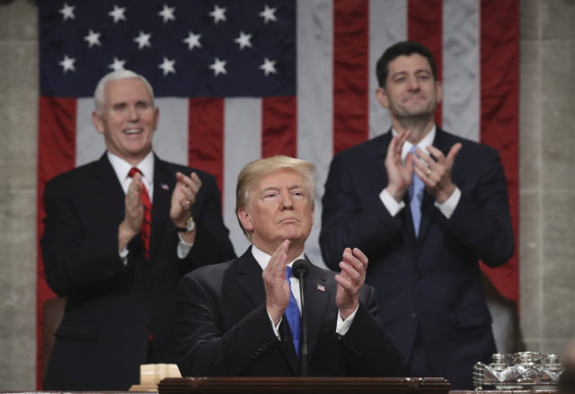 President Donald Trump pauses as he gives his first State of the Union address in the House chamber of the U.S. Capitol to a joint session of Congress Tuesday, Jan. 30, 2018 in Washington, as Vice President Mike Pence and House Speaker Paul Ryan applaud. (Win McNamee/Pool via AP)