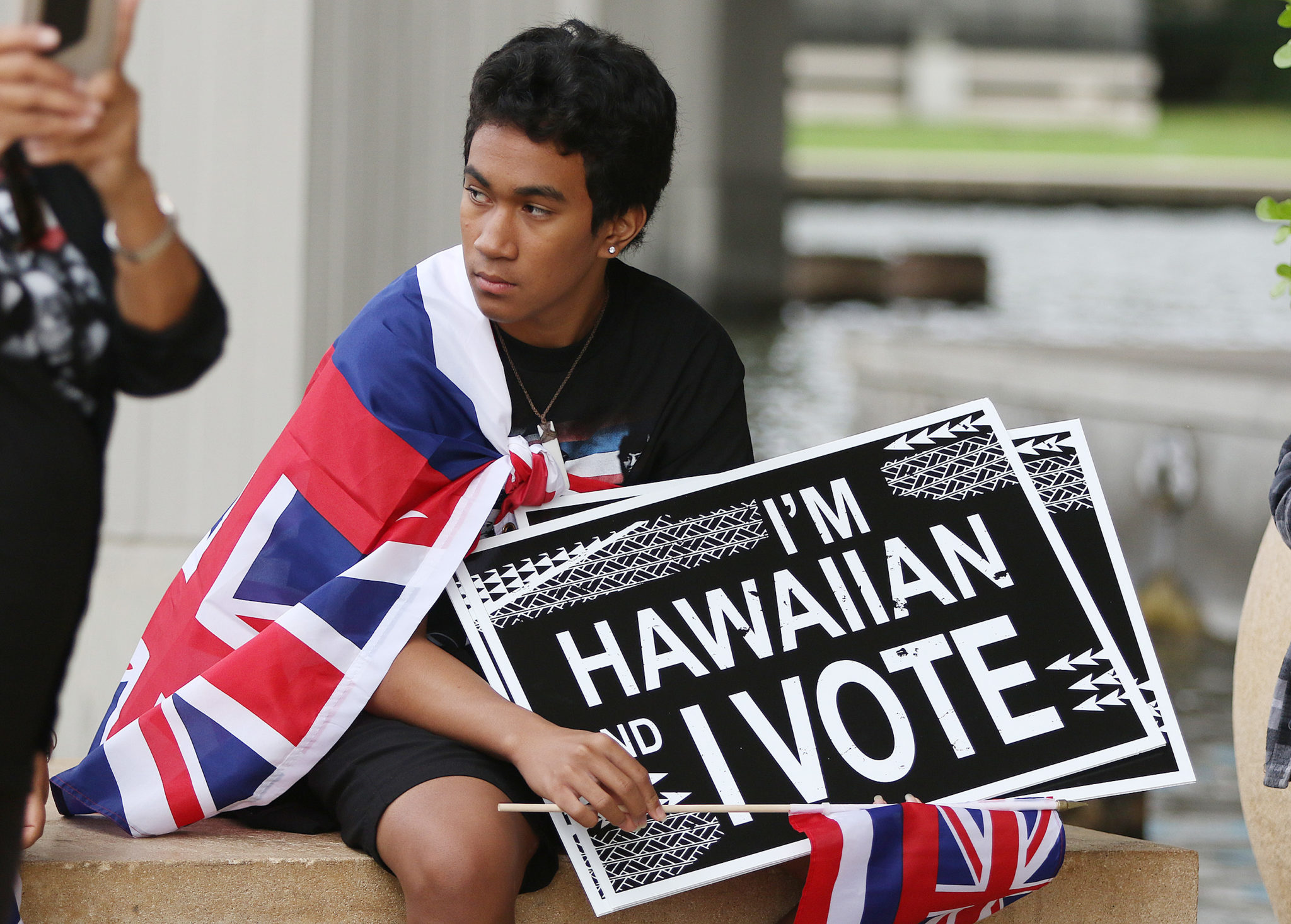 <p>Cross Su'e-Kepilino, 16, was among the sign-bearers inside the Capitol Rotunda, where voter registration information was handed out.</p>