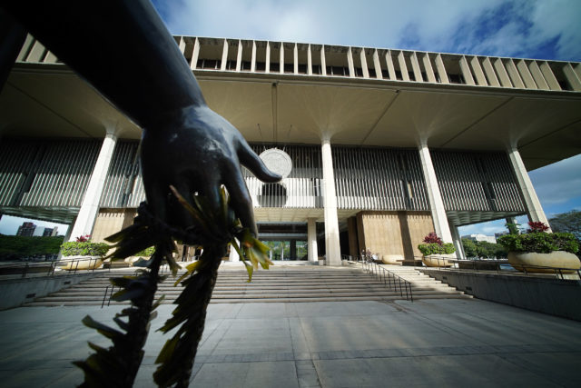 Lei bedecked bronze hand of Queen Liliuokalani on the makai side of the Hawaii State Capitol building.