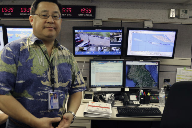 FILE - In this July 21, 2017 file photo, Jeffrey Wong, the Hawaii Emergency Management Agency's operations officer, shows computer screens monitoring hazards at the agency's headquarters in Honolulu. The photo originally accompanied an Associated Press story in July about Hawaii preparing for a missile threat from North Korea. Some online news organizations used the AP photo in their coverage of the Jan. 13, 2018 false missile alert in Hawaii, leading some people to believe Wong was the person who sent the false alert. The AP did not use the image in coverage of the false alert. Wong says he has received threats and harassment because of the use of the image online. (AP Photo/Jennifer Sinco Kelleher, File)