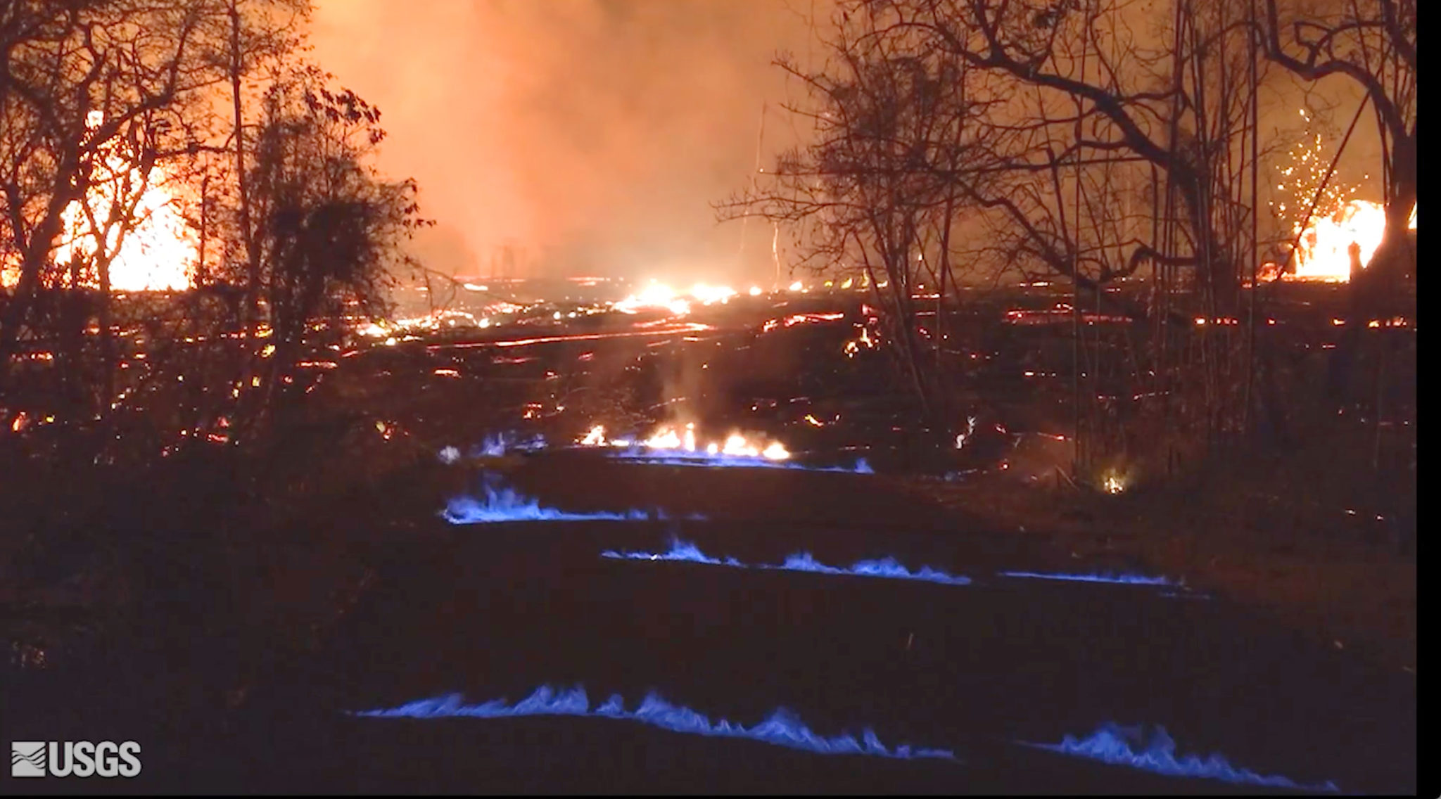 This photo from video from the U.S. Geological Survey shows blue burning flames of methane gas erupting through cracks on Kahukai Street in the Leilani Estates neighborhood of Pahoa on the island of Hawaii during the overnight hours of Wednesday, May 23, 2018. When lava buries plants and shrubs, methane gas is produced as a byproduct of burning vegetation. Methane gas can seep into subsurface voids and explode when heated, emerging from cracks in the ground several feet away from the lava. (U.S. Geological Survey via AP)