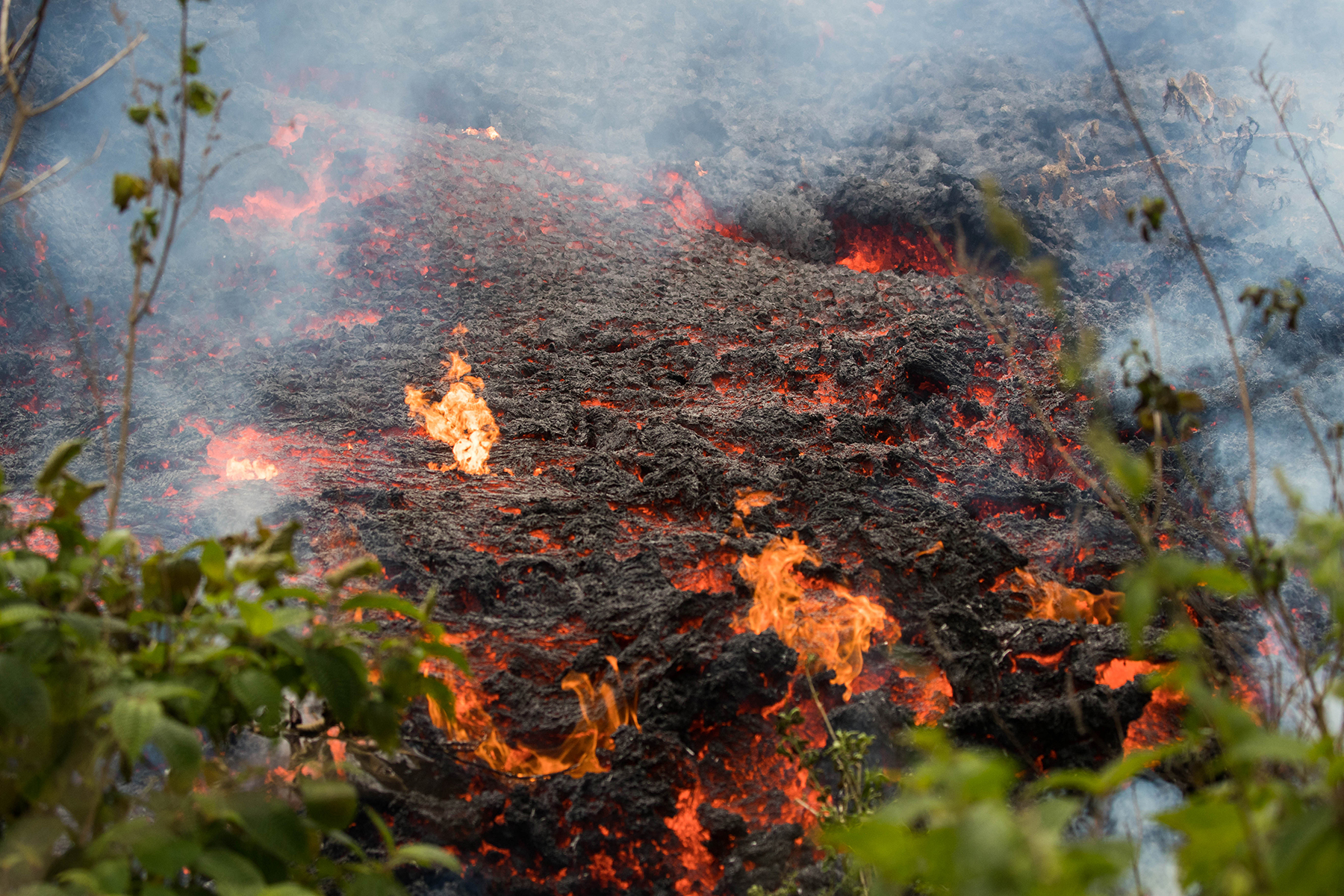 <p>Nearby brush begins to burn as the lava flows intensify in the Puna area of the Big Island on Saturday.</p>