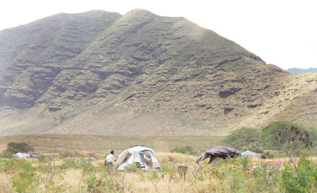 Al heads back to his tent with the Waianae Mountains in background on parcel of land off of Lualualei Road in waianae.