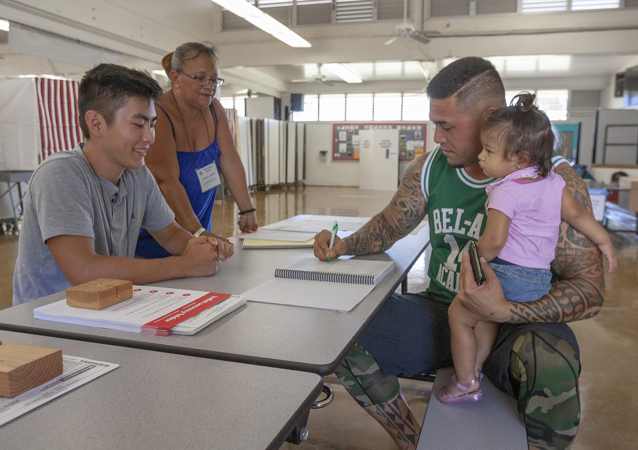 <p>Voter precinct volunteers Tyler Maruno, left, and Letitia Corpuz help Matt Coleman, holding his daughter Natalee, sign in before voting at Lanakila Elementary School.</p>