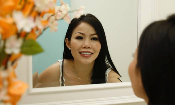 Patient looking at her smile in the mirror