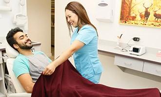 Staff putting blanket on patient