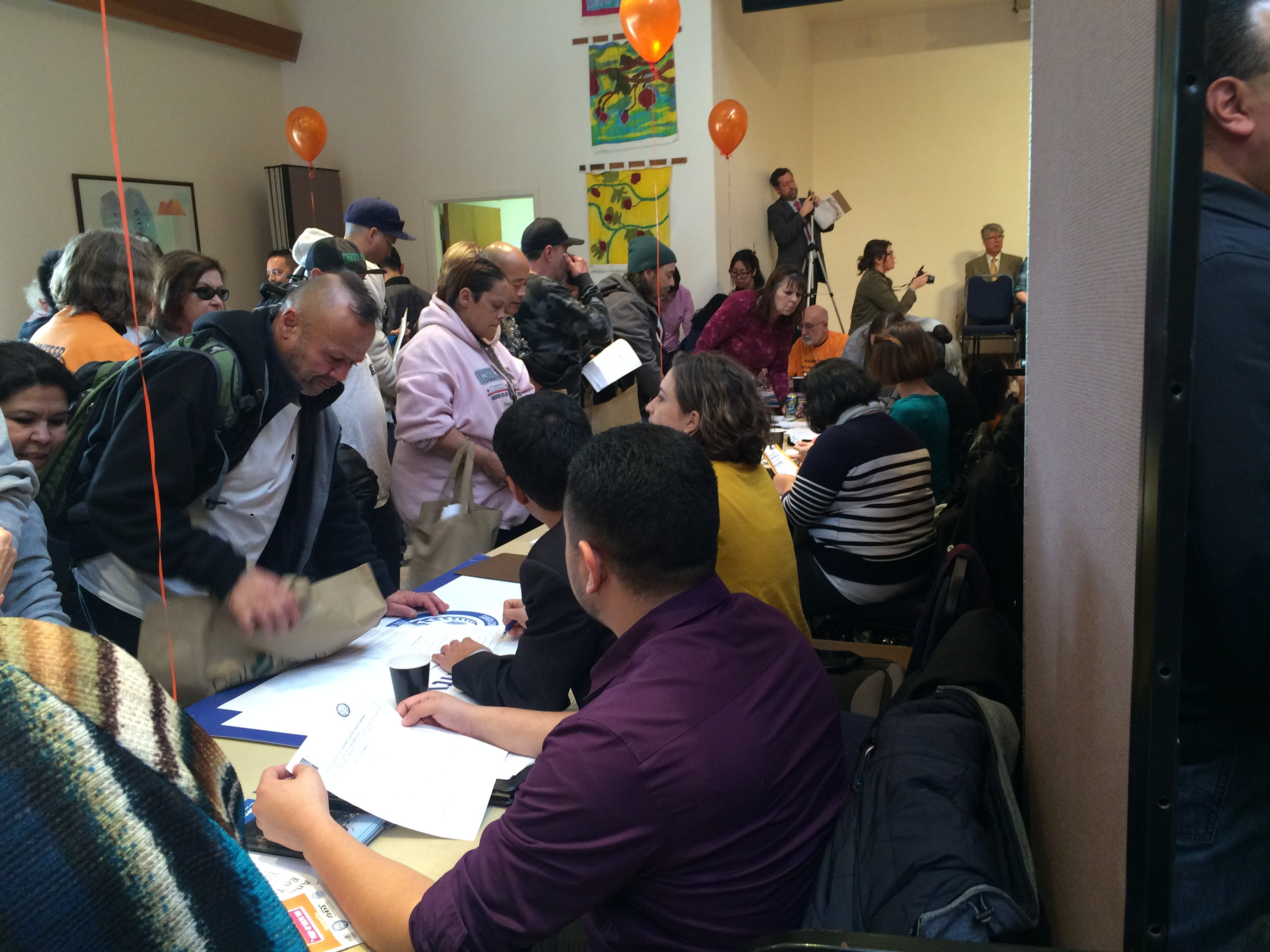 <p>People crowd around the public defender's table to ask about changing their records at a reclassification fair in Santa Cruz.</p>