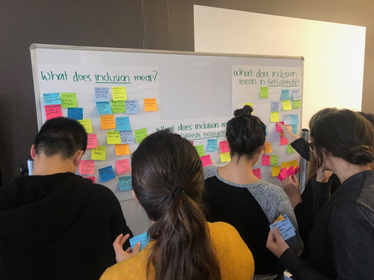 Group of people placing Post-Its on a whiteboard about what inclusion means to them, and what it means in GetCalFresh