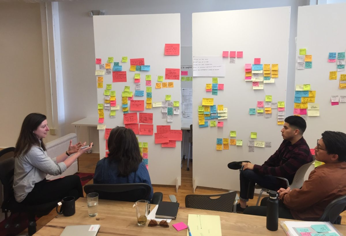 Researchers sitting in front of a white board with many Post-Its