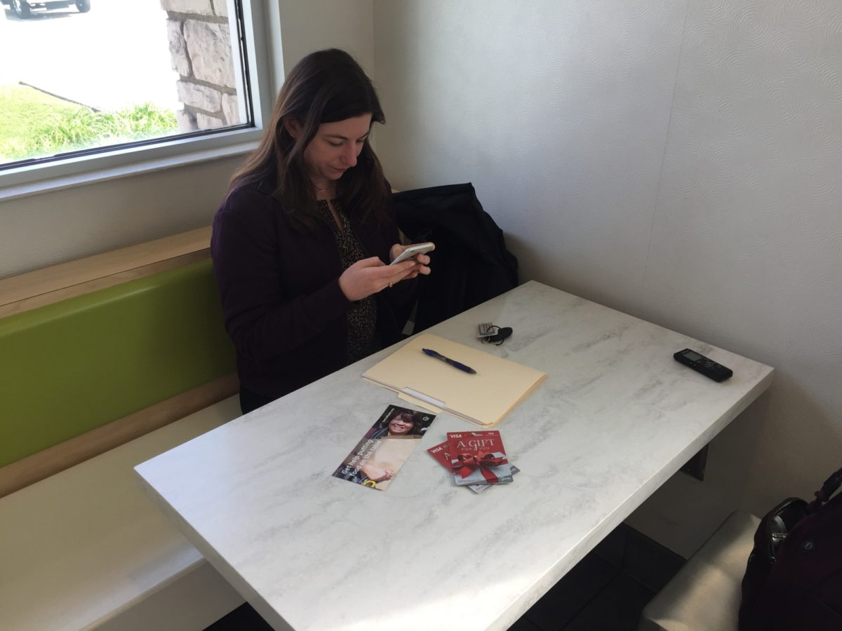 Researcher sitting at a table with a pen, paper, and Visa gift cards