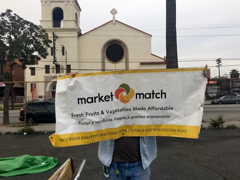 Person holding large market match sign in front of church