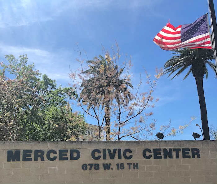 Merced civic center sign and an American Flag