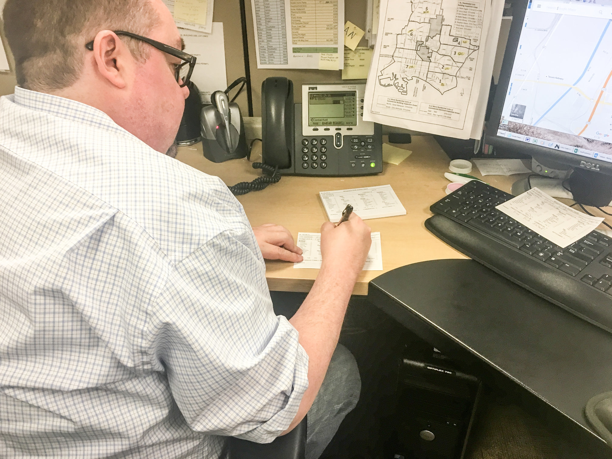 <p>Permit Technician Mike M. transcribing inspection requests from voicemail.</p>