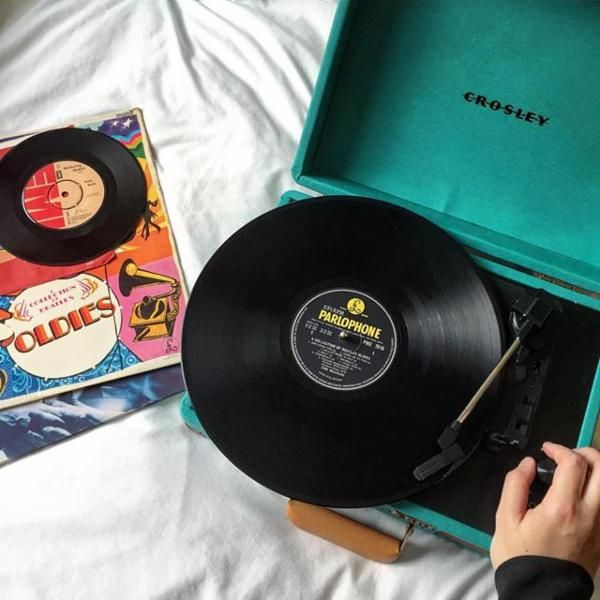 Vinyl recorder on a bed playing 'A Collection of Beatles Oldies'