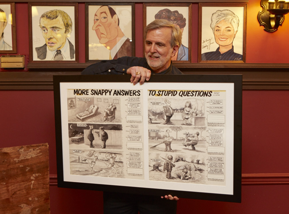 MAD Art Director Sam Viviano holding an original piece of Al Jaffee's artwork from the 1960s gifted to Al by DC Entertainment