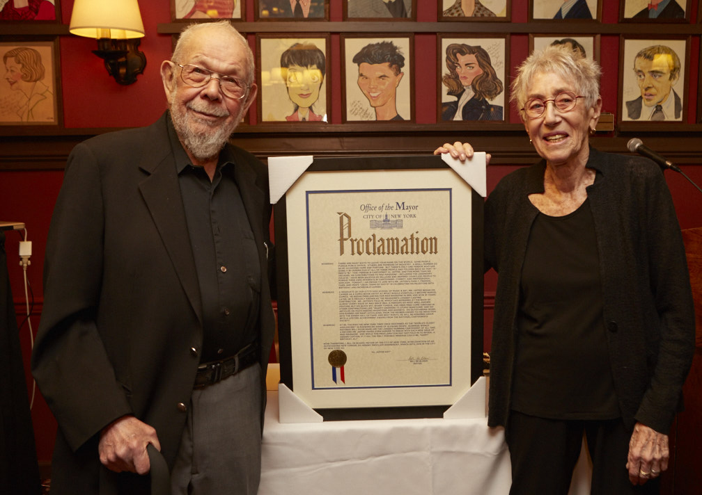 Al and Joyce Jaffee standing with the proclamation from NYC Mayor Bill DeBlasio proclaiming March 30th, 2016 as Al Jaffee Day