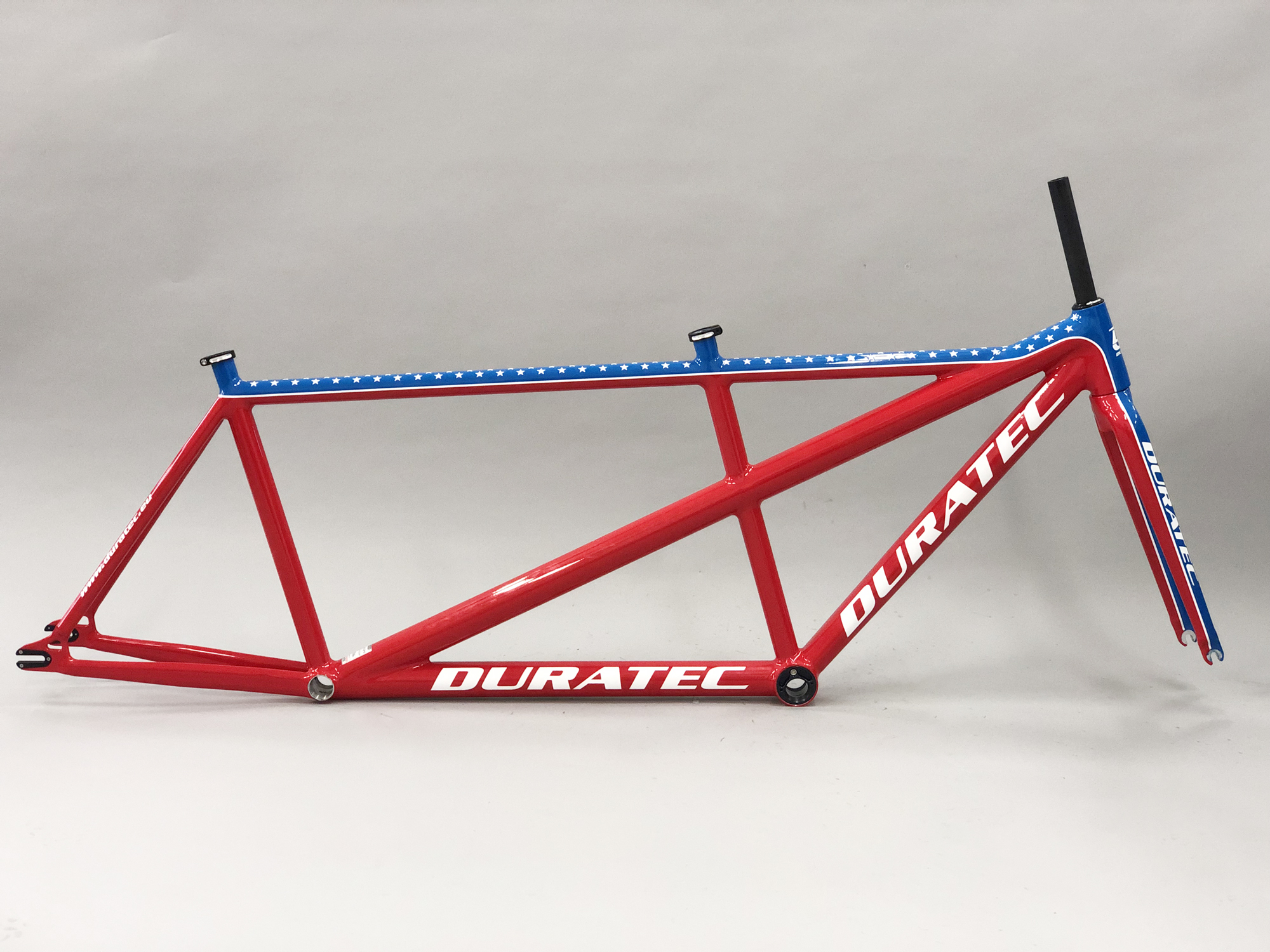 Bright red tandem frame with DURATEC emblazoned on it. Across the top white stars on a royal blue background. The frame has no saddles, pedals, handbars, gears or chains attached
