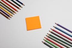 ألوان خشبية على خلفية بيضاء مع ورق ملاحظات