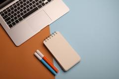 دفتر ملاحظات مع ألوان بالقرب من جهاز اللابتوب