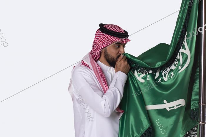 سعودي يقوم بتقبيل العلم السعودي