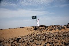 شاب سعودي في الصحراء حامل لراية المملكة العربية السعودية