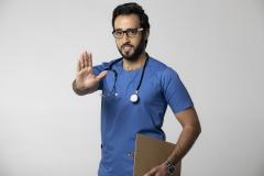 طبيب سعودي يلوح بيده بعلامة توقف