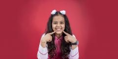 طفلة مبتسمة بزي المدرسة السعودية