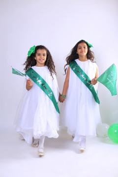 طفلتين يحتفلون باليوم الوطني السعودي