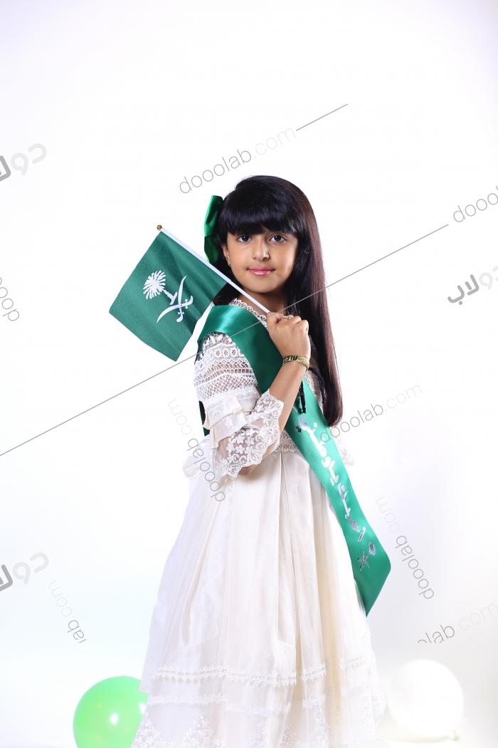 فتاة جميلة حاملة للعلم السعودي