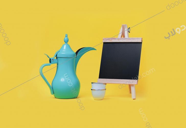 لوحة طباشيرية سوداء ودلة قهوة عربية مع فنجالين