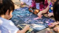 Preschool students drawing together with chalk on a large slate board