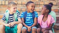 Three elementary school children wearing backpacks, sitting on the school steps, talking and laughing together