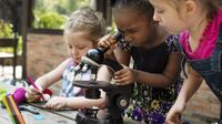 Three kindergarten students doing a science lab. The girl in the middle is looking into a microscope and the other two girls are looking on and writing things down on paper with markers.