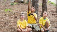 Three elementary school children kneeling on the ground in a forest. One is holding a pair of binoculars and pointing upward toward the trees. The other two are looking up to where he's pointing.