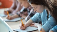 Students writing in notebooks in class