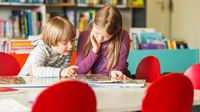 Two kids of different grade levels reading together in a library