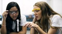Two students doing a chemistry experiment with a test tube in a school science lab